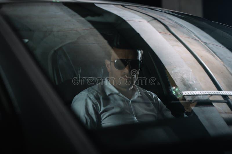 agente segreto maschio in occhiali da sole che si siedono in automobile con la tazza di caffè della carta mentre facendo fotografie stock