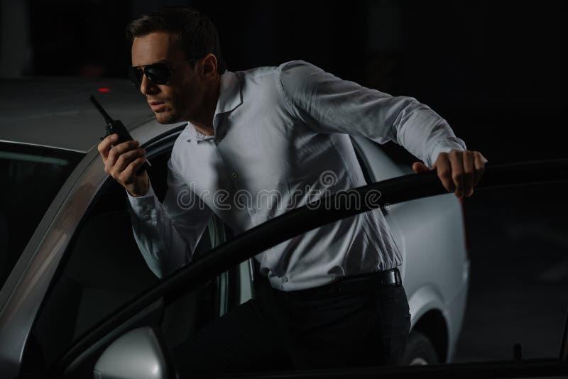 agente segreto maschio in occhiali da sole facendo uso del walkie del talkie fotografia stock