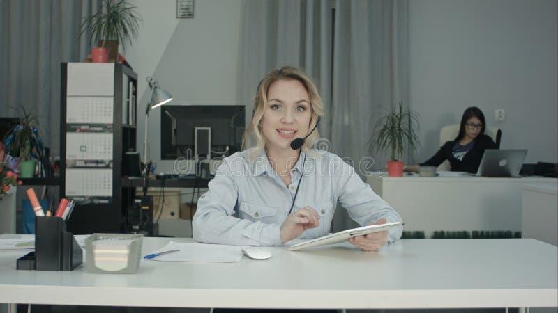 Agente sonriente del centro de atención telefónica usando la tableta y el hablar con la cámara imagen de archivo