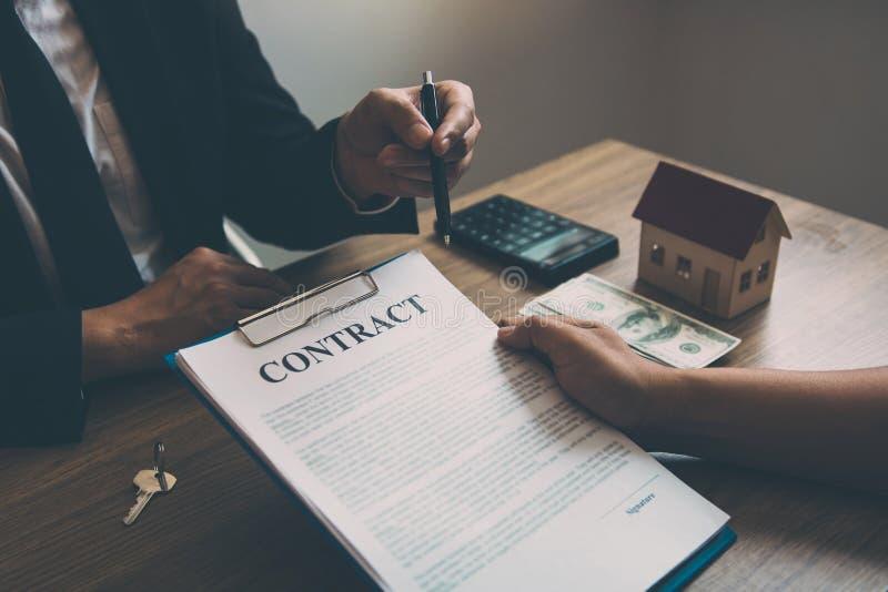 Agentes del hogar hablando con compradores del hogar que están firmando contratos en la oficina fotos de archivo libres de regalías