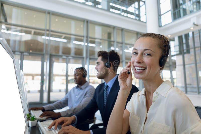 Agentes do centro de chamada que trabalham no escritório de plano aberto imagem de stock