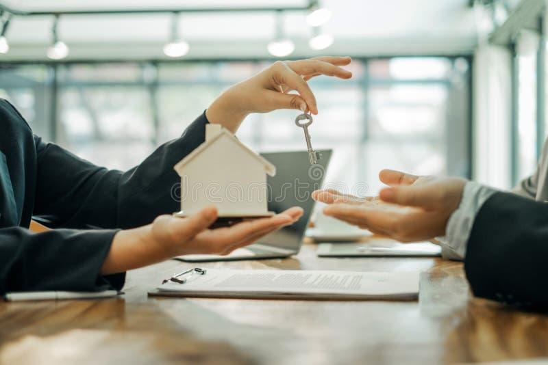 Agentes imobiliários com modelo e chaves para apresentar documentos para os clientes assinarem um contrato de venda, conceito de  imagens de stock