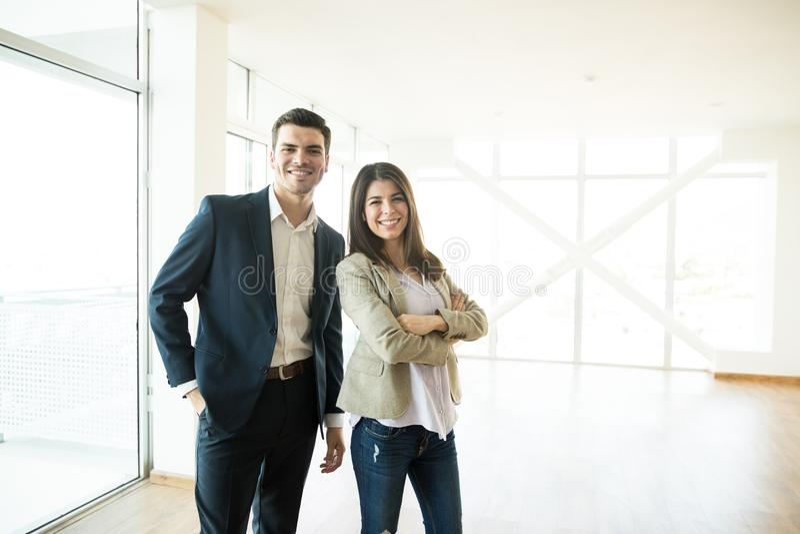 Agenti immobiliari sorridenti che stanno in nuovo appartamento fotografie stock