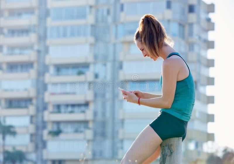 Agentmeisje die een rust hebben en smartphone gebruiken stock afbeelding