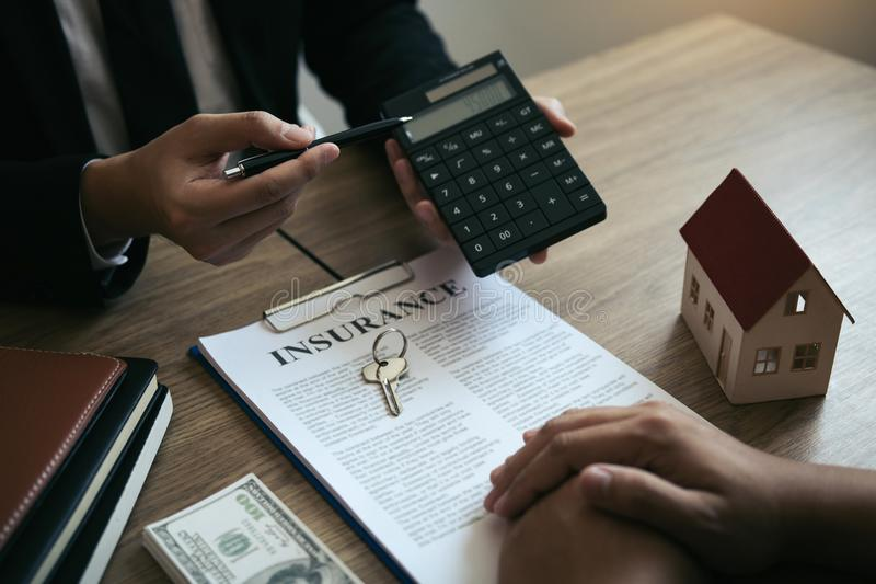 Agents are calculating the loan payment rate or the amount of insurance premiums for customers coming to contact the purchase of a. New home at the office stock photography