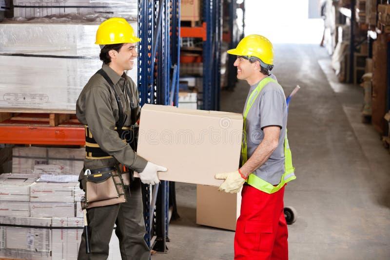 Agents de maîtrise portant la boîte en carton à l'entrepôt photographie stock