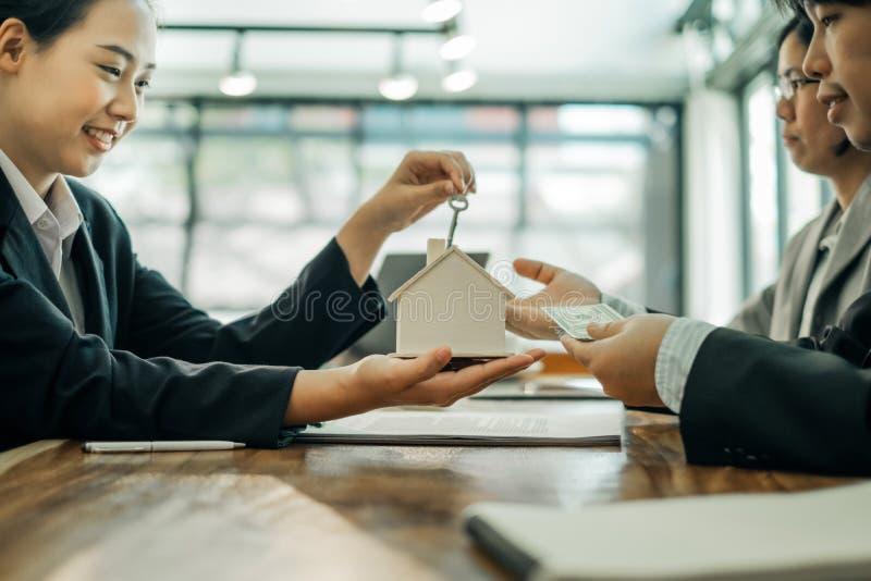 Agents immobiliers détenant des maquettes de maison et des clés pour soumettre des documents à signer pour les clients pour un co photographie stock libre de droits
