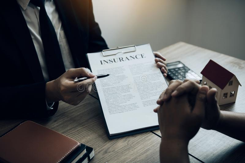 Agents are using pens pointing to insurance contracts and are being explained to customers at the office.  stock photography