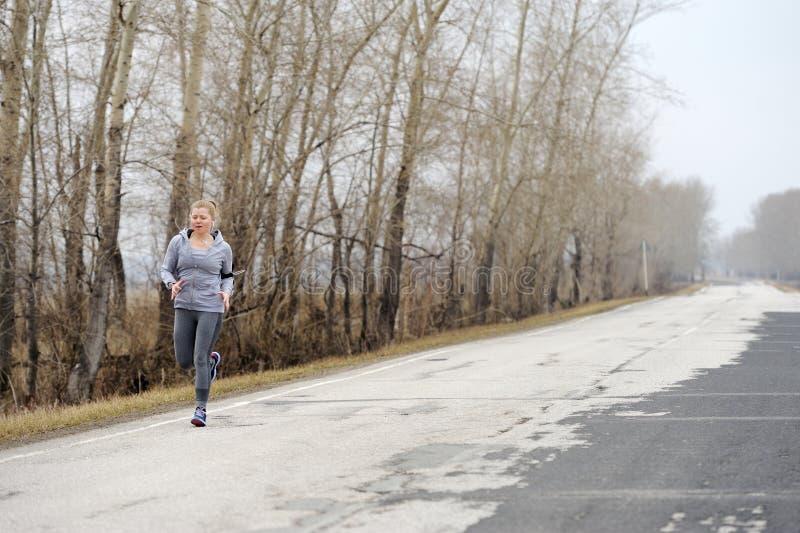 Agentvrouw die op weg in mooie aard lopen Joggingtraini stock afbeeldingen