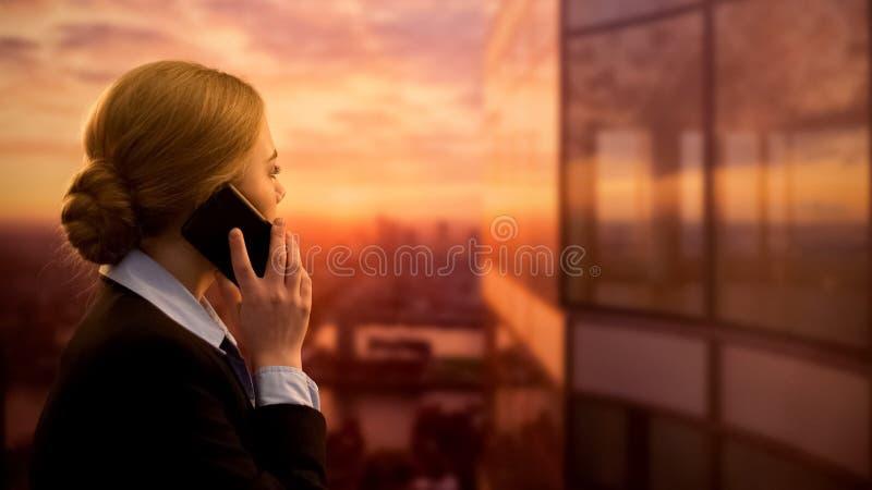 Agenzia di viaggi di chiamata femminile, viaggio di affari di prenotazione, godente del paesaggio urbano di tramonto immagine stock libera da diritti