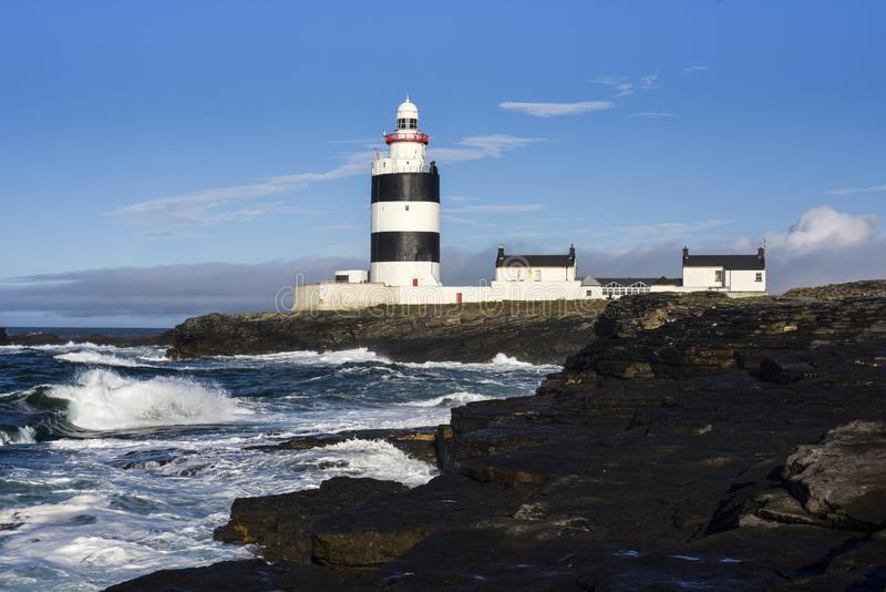 Agganci il faro capo situato sulle scogliere con le onde di morbidezza e del mare, il cielo blu, la contea Wexford, Irlanda fotografia stock libera da diritti