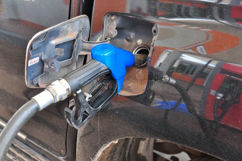 Aggiunga l'olio combustibile all'automobile nella pompa del carburante con un erogatore selec fotografie stock