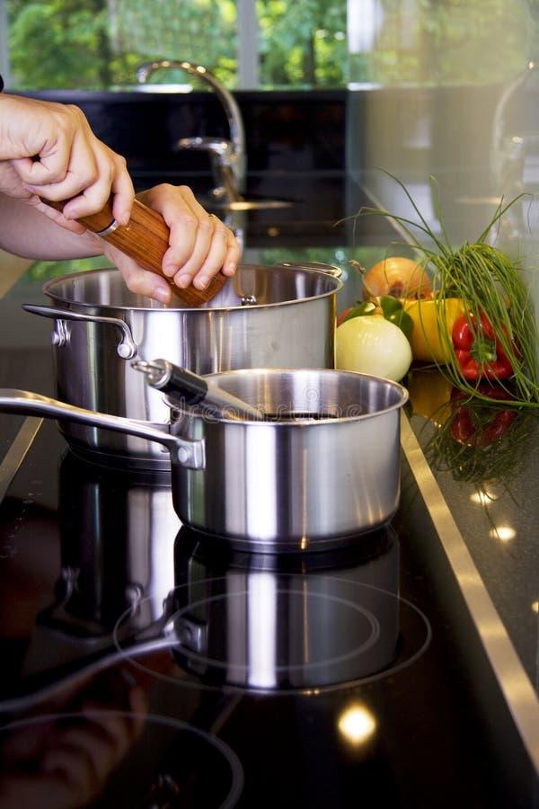 Aggiungendo pepe al pasto immagine stock