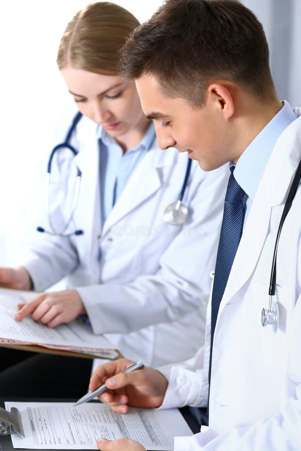 Aggiusta le carte da lettere facendo uso della lavagna per appunti Medici che discutono programma del farmaco o che studiano alla fotografia stock libera da diritti