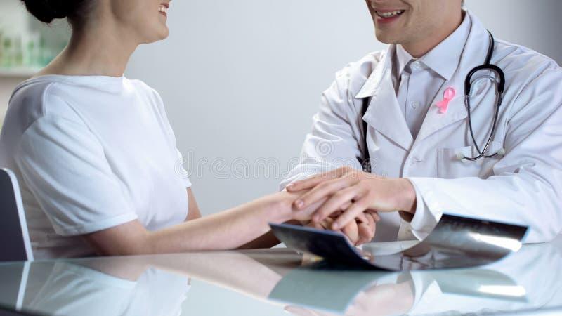 Aggiusti felice di dire le buone notizie pazienti circa il risultato di mammogramma, entrambi che sorridono immagine stock