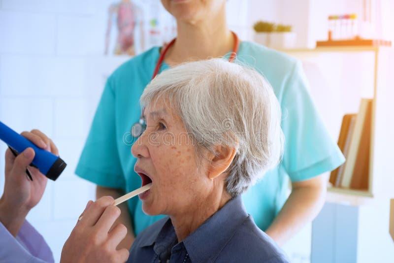 Aggiusti il controllo della gola d'esame della donna senior con la torcia elettrica fotografia stock libera da diritti