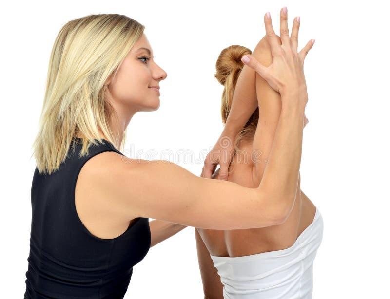 Aggiusti il fisioterapista che allunga una giovane donna di sport isolata fotografia stock