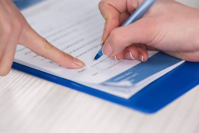 Aggiusti indicare al documento ed al paziente che firmano il contratto medico fotografie stock