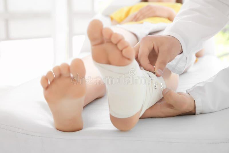 Aggiusti l'applicazione della fasciatura sulla gamba paziente del ` s in clinica immagini stock
