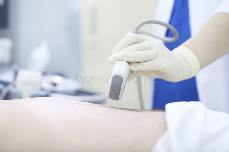 Aggiusti l'esame ecografico di conduzione dell'addome ad un paziente fotografie stock