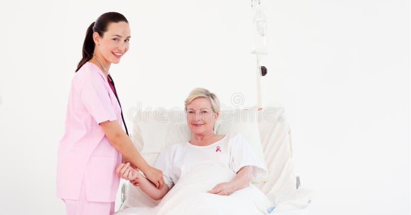 Aggiusti la donna con il paziente con il nastro di consapevolezza del cancro al seno fotografia stock