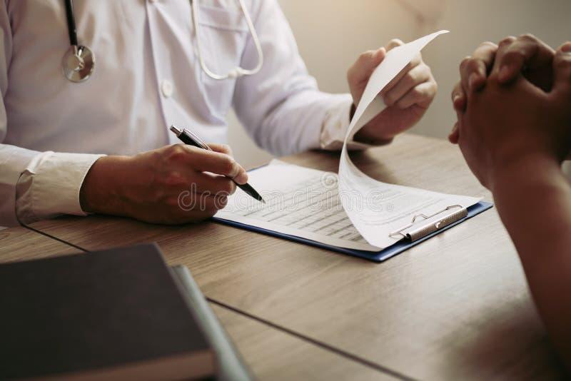 Aggiusti la lista di storia del paziente di scrittura della penna di tenuta della mano sul blocco note e la conversazione con paz immagine stock libera da diritti