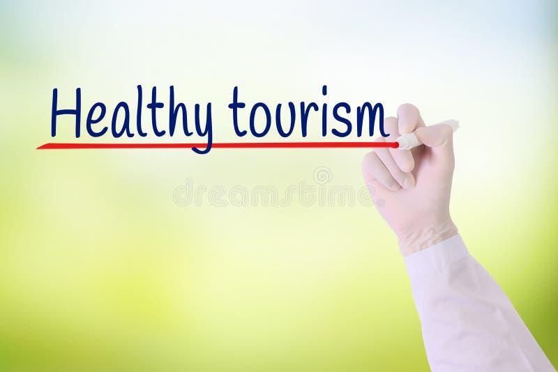 Aggiusti la mano con turismo di salute di scrittura del guanto sopra fondo vago verde fotografia stock libera da diritti