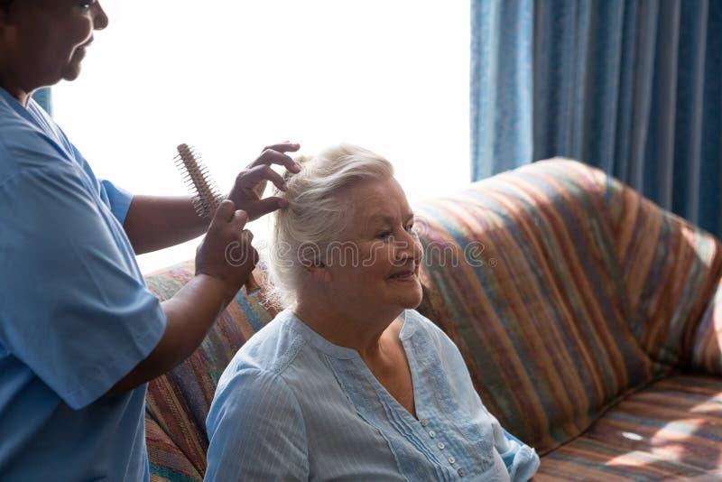 Aggiusti la pettinatura dei capelli del paziente nella casa di cura immagini stock