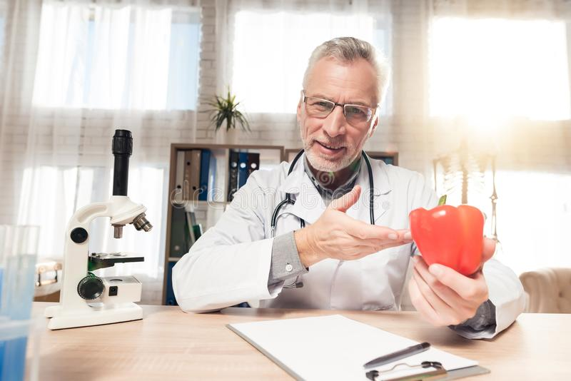 Aggiusti la seduta allo scrittorio in ufficio con il microscopio e lo stetoscopio L'uomo sta tenendo il peperone immagine stock