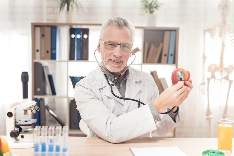Aggiusti la seduta allo scrittorio in ufficio, mela d'ascolto con lo stetoscopio fotografia stock libera da diritti