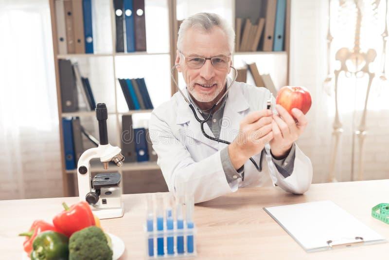 Aggiusti la seduta allo scrittorio in ufficio, mela d'ascolto con lo stetoscopio immagine stock