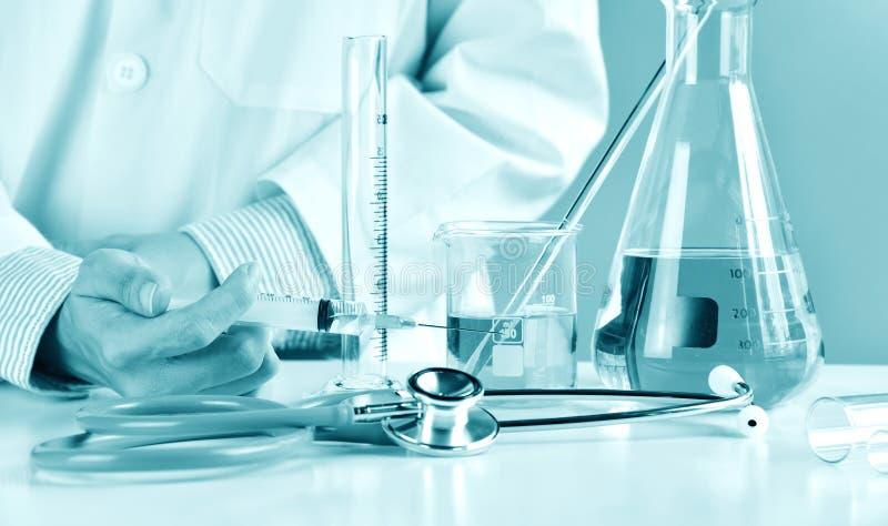 Aggiusti la siringa della tenuta con il vaccino medicinale, vetreria per laboratorio immagini stock libere da diritti
