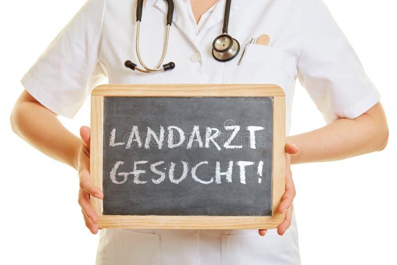 Aggiusti la tenuta della lavagna con la parola tedesca fotografia stock