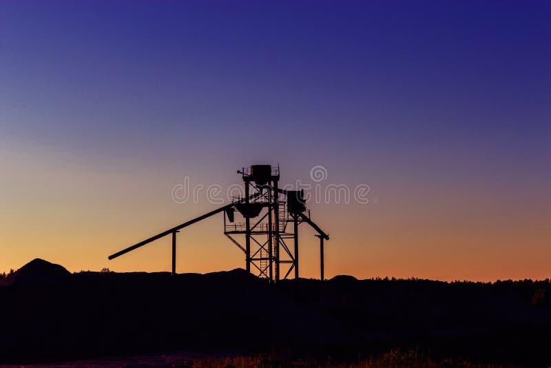Agglomération de construction près des amas de gravier au coucher du soleil images stock