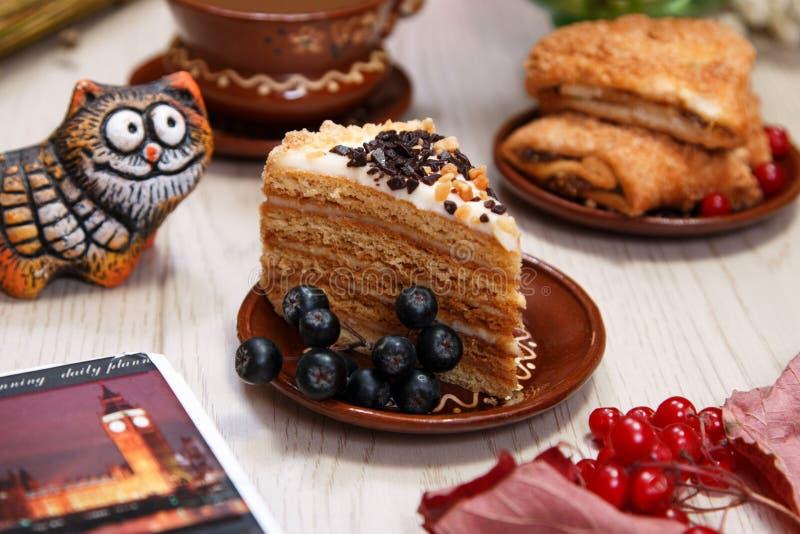 Agglutini, biscotti della frutta, viburno, chokeberry e figurina rossa del gatto sulla tavola Piatti di argilla Vista laterale Fi immagini stock