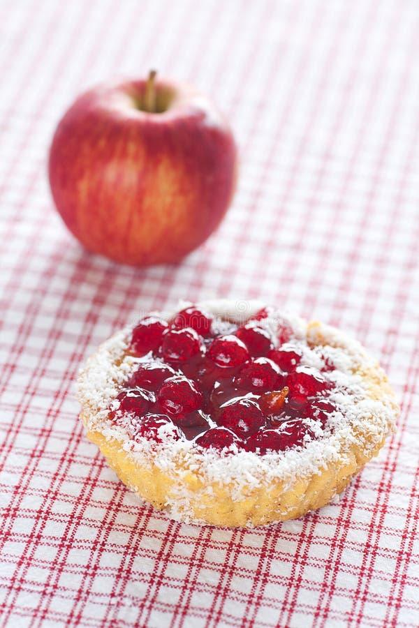 Agglutini con le bacche e la mela sul tessuto del plaid immagine stock