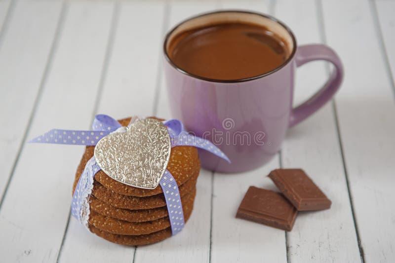 Aggredisca con i biscotti del pan di zenzero completati cacao caldo, il ricordo metallico del cuore e di pepita di cioccolato su  immagine stock