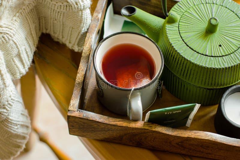 Aggredisca con il tè rosso caldo della frutta, i sacchi di carta, vaso verde in trey, maglione tricottato bianco che appende sopr immagini stock