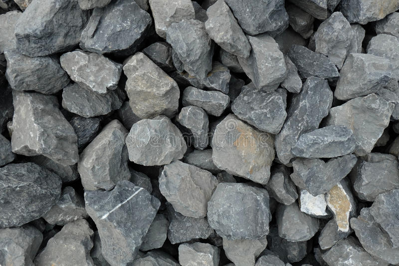 Aggregate of very large coarse gray stones, crushed at a stone pit, gravel pattern. A closeup of a pile of loose rough stones taken at a stone pit. The gravel / stock photos