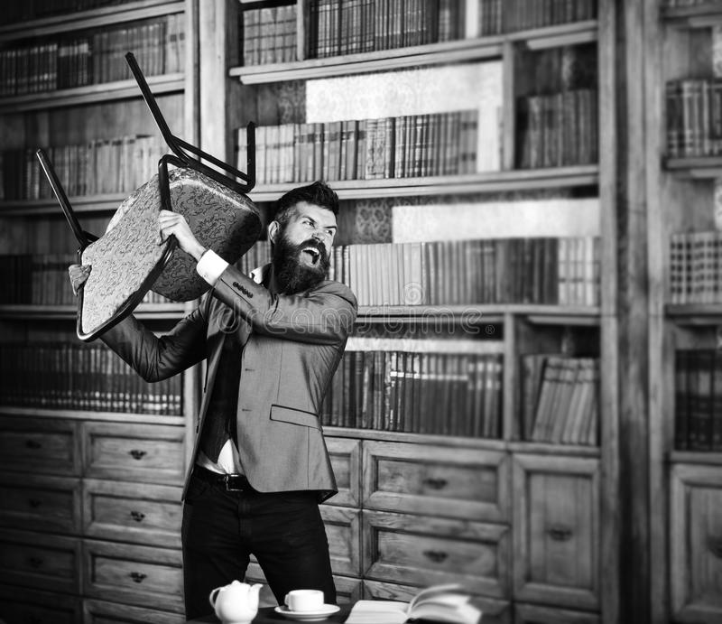 Aggression, hate, nervous, negative emotions concept. Man with angry face holds chair and ruins library. Bearded man in. Formal suit screams near bookcase royalty free stock images