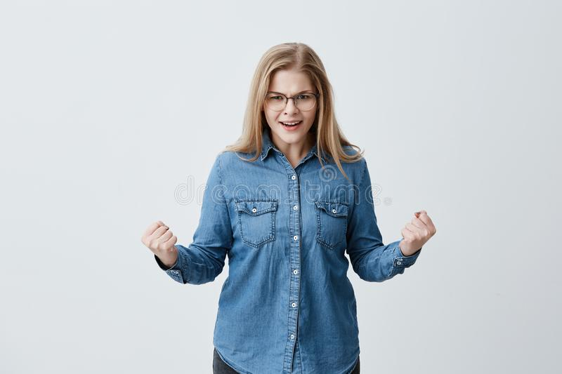 Aggression, negative human reaction and attitude. Angry stressed out blonde female in eyeglasses, denim shirt screaming stock images