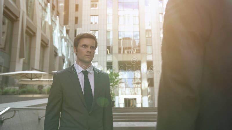 Aggressiv kontorsarbetare som ser kollegan, ansträngning för arbetsplats, rivalitet arkivfoto