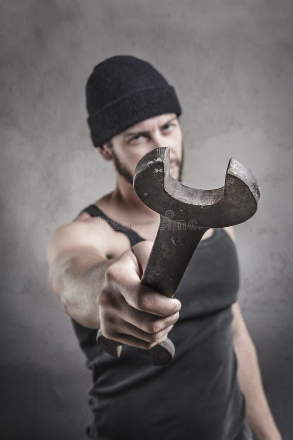 Aggressiv man som använder en skiftnyckel som ett vapen royaltyfri bild