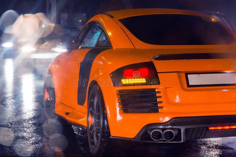 Aggressiv och brutal orange sportbil på den regnade vägbilden som är användbar för bakgrund arkivfoton