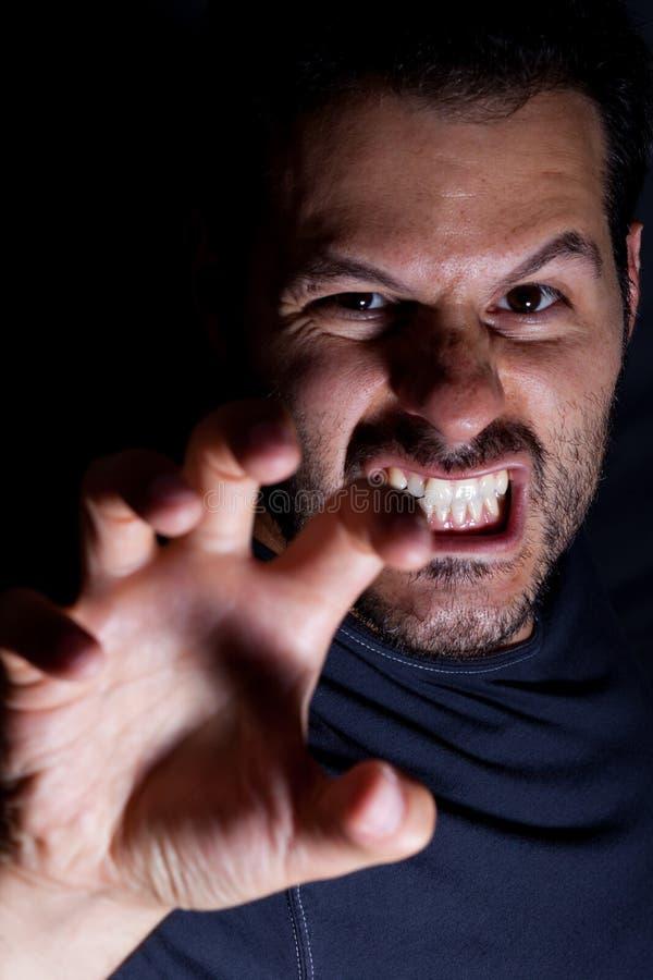 Aggressiva manattacker med hans hand i en läskig nattplats royaltyfri fotografi