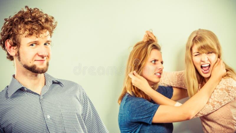 Aggressiva tokiga kvinnor som slåss över man arkivfoto