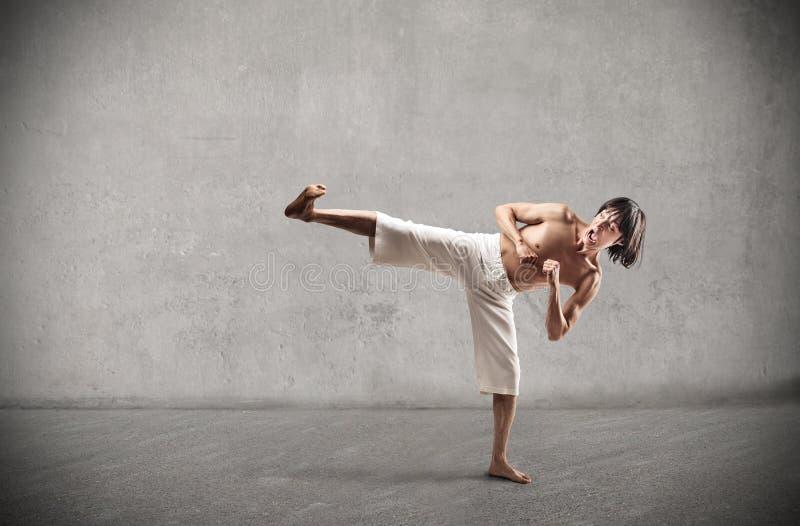 Aggressive asian man. Doing karate stock photography