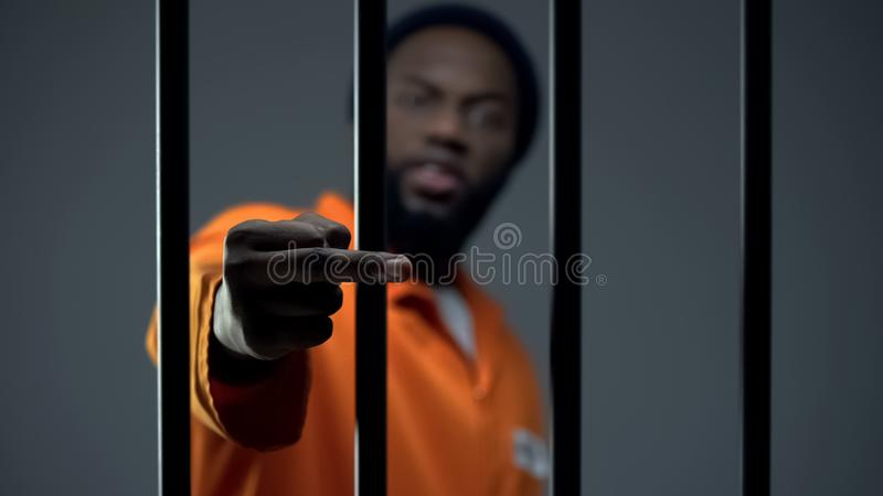 Aggressive black prisoner showing medium finger, dangerous criminal imprisoned royalty free stock image