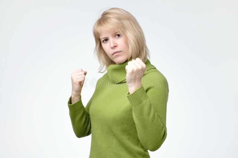 Aggressive blonde woman standing in boxer pose. Fight and dangerous concept. Aggressive blonde woman standing in boxer pose. Studio shot, isolated on gray stock photo