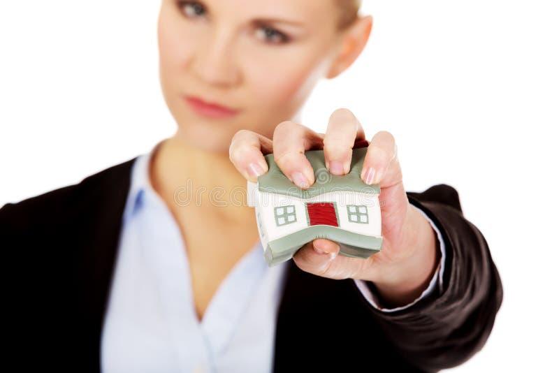 Aggressive Geschäftsfrau, die kleines Haus zerquetscht lizenzfreies stockfoto